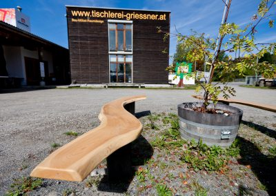 Wellenbank aus Holz vor dem Gebäude der Tischlerei Griessner